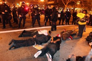Several protesters lie face down on the ground in front of of riot