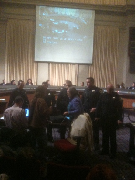 5 Oakland police officers surround one lone women who expressed outrage at the City Council voting to extend a contract to former LA and NY police chief William J Bratton